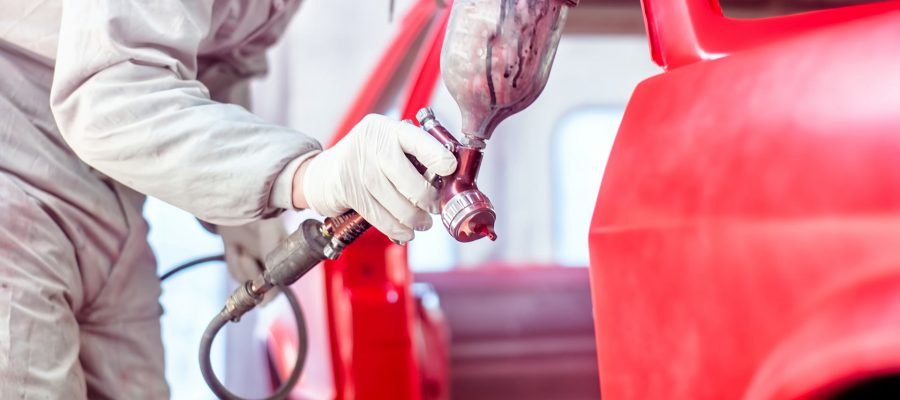 professional-worker-spraying-red-paint-on-a-car-P95UYUS